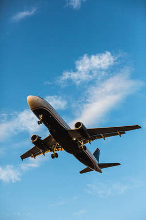 transportaion: Airplane flying with blue sky in background on a sunny afternoon