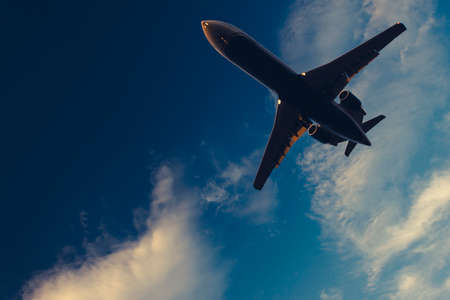 Underneath Airplane with pretty blue sky and clouds in background