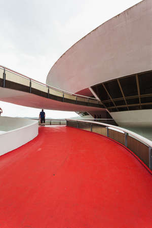 comtemporary: Exterior and entrance of Niteroi art museum with people walking through up the path