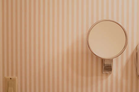 mirror on wall: round mirror fixed to the wall of bathroom with peach striped wallpaper Stock Photo