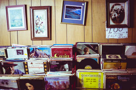 vintage paintings and pictures hanging on wooden wall, with heaps of vinyls stackedd in shelves