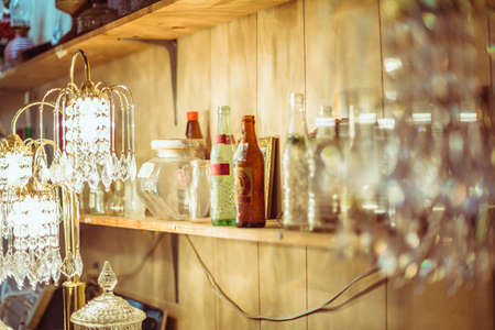 glasswear: cluttered shelf with bottles and containers in vintage shop Stock Photo