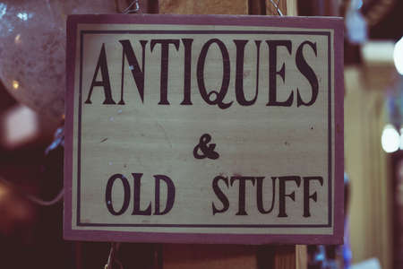 Antiques & old stuff sign hangig in an antique store Archivio Fotografico