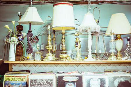antique lamps sitting on shelf with records underneath