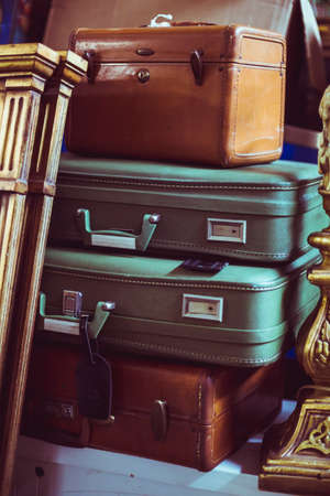 thrift box: stack of brown and green leather suitcases in an attic