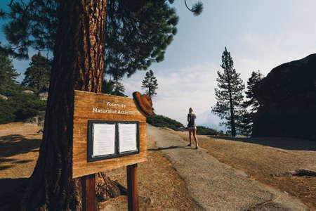 naturalist: Sign for Yosemite Naturalist Activities and girl walking up path