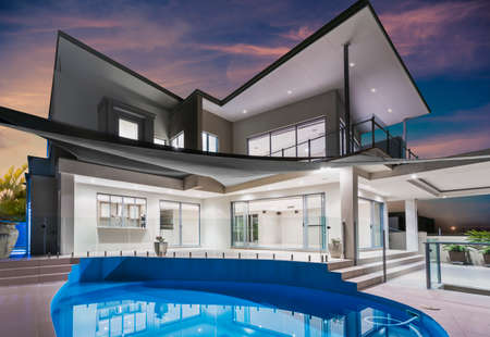 Modern new luxurious mansion exterior with swimming pool and reflections at dusk with pink and blue sky on the Gold Coast, Queensland, Australia