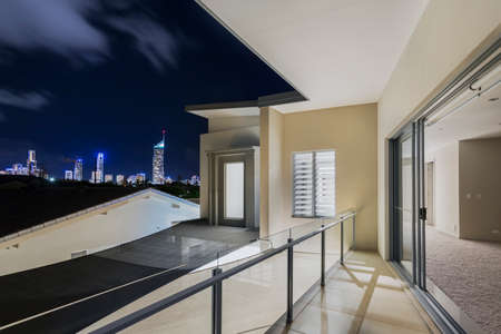 gold coast: Master bedroom with balcony overlooking city skyline at night over Surfers Paradise Gold Coast Queensland Australia