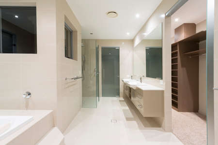 walk in closet: Spacious contemporary bathroom with spa and walk in robe