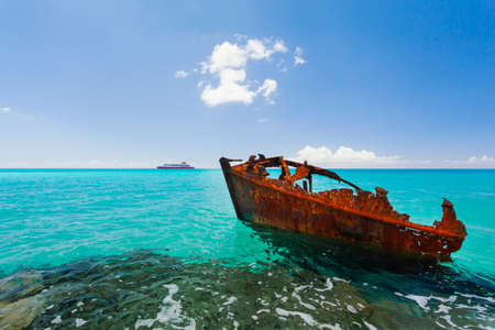 ship wreck: Red rusty ship wreck on rocks in turquoise tropical waters Stock Photo