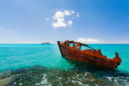 vacaciones en la playa: Rojo naufragio de un barco oxidado en las rocas en aguas tropicales turquesa