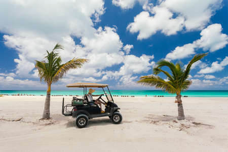 Woman riding in a golf cart on the beach. photo
