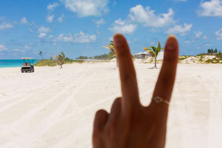 Hand doing peace sign with beach background photo