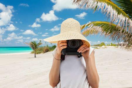 Caucasian woman taking pics on the beach on tropical island photo
