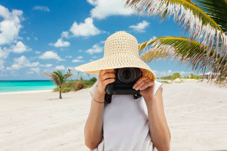pics: Caucasian woman taking pics on the beach on tropical island