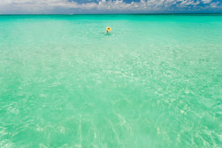 Tourist swimming in crystal clear waters of Bahamas in sunlight photo