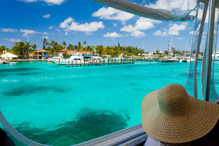 Woman in boat looking out to tropical island with harbor photo
