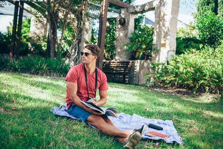 Handsome young man kicks back in his local park, relaxing, reading a magazine and testing out his vintage camera on the lush green surroundings. Stock fotó