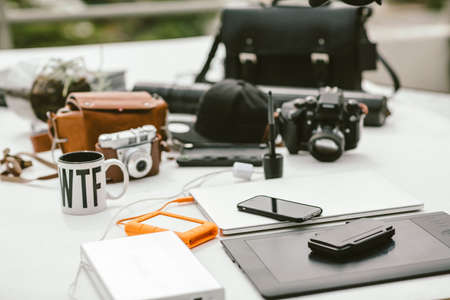 Table with photography gear, camera bags, laptop, external laptop power, external rugged hard drive and tablet. Stock fotó