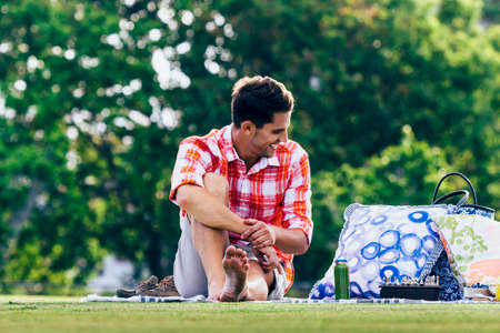 food testing: There is nothing better than laying down a blanket and picnicing with your girl in the park on summers day.  Relaxing, feasting on delicious food and testing on the new chess set. Stock Photo