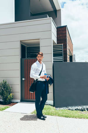 Stylish young professional standing outside his modern terrace apartment. Ready for work, armed with his morning coffee, suit jacket and messenger bag. Stock fotó