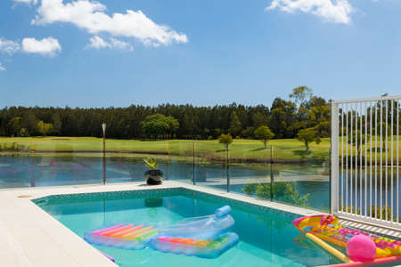 Luxury waterfront living with swimming pool, floats and Inflatable colorful toys on a sunny summers day