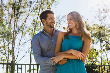 Handsome young man with his arms around an attractive young woman outside on a sunny day.