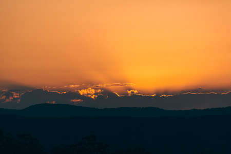 Sunset over the Sunshine Coast hinterland.  We watch as the sun disappears behind the clouds, its golden rays set fire to the fragile edges of the clouds.