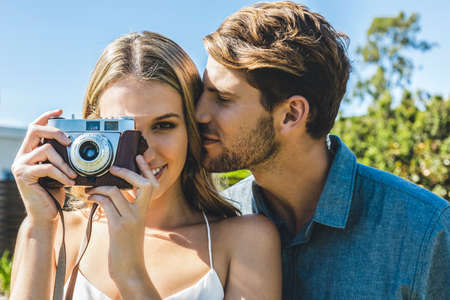 Young attractive in love couple taking pictures outside with a vintage camera. Stock fotó