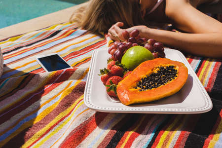 Crop of a woman sunbaking by the pool with a fresh fruit platter and an iPhone. Stock fotó