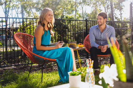 Young attractive caucasian couple relaxing in the garden at home.