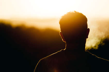 Silhouette of man smoking and watching the orange sun set Stock fotó