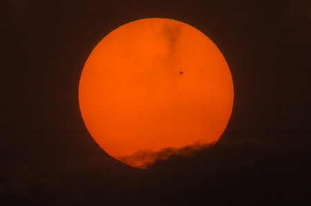 sunspot: Real picture of the sun with a big sunspot group over the dark cloud Stock Photo