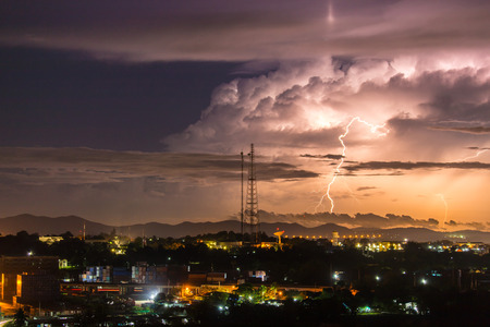striking: Sky with lightning striking hills behind small town