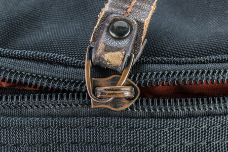 reachability: Old and damaged zipper on black cloth Stock Photo