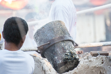 metal casting: Worker pouring molten metal to casting Buddha statue Stock Photo