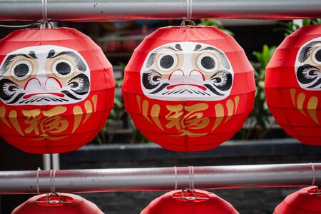 "Daruma dolls. The Japanese lucky symbolic dolls hanging in the row with text translation ""fortune""."