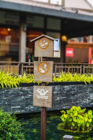 No smoking,Dont Feeding fish and Careful Drowning. Safety wood Signs in the park Stock Photo