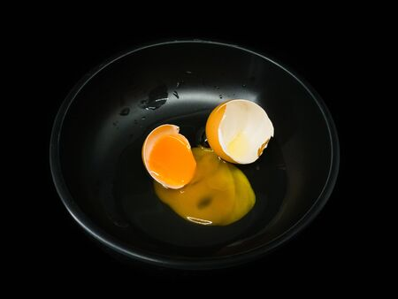 low key image of a raw organic egg cracked open onto a black cup and black background