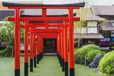 Red and orange tori tunnel in Fushimi Inari Shrine in Thailand with japan style gate. It is one of the most famous place for tourist.