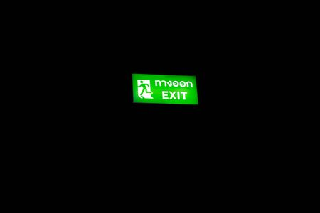 A Occupational Safety and Health Signs with dark background. Thai and English Spelling. English Translate; Exit. Stock fotó