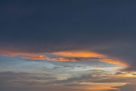The Bright orange and gold colors of the sunset sky. Summer sky with clouds during the sunset