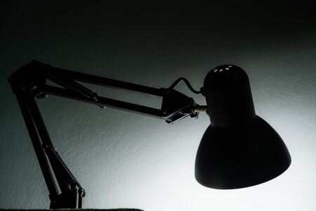 The Silhouette of a table lamp on the background of a window in the morning at dawn, work until morning, work at night.