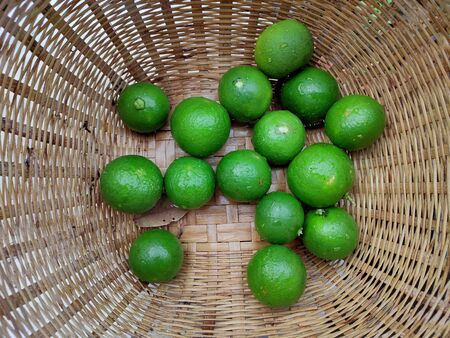 The Fresh green limes in the small colorful baskets on the woven bamboo plate. The Thai traditional fresh market.