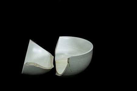 The Pieces of broken white ceramic bowl on black background. Copyspace, place for text. Break, fragment.