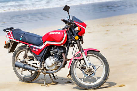 Hainan Shenzhou Peninsula, China - February 13, 2017: Used red model Suzuki GS125 motorcycle parked at tropical beach Editorial