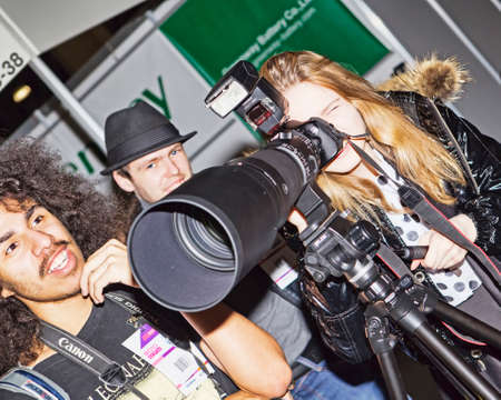 EXHIBIDOR: Moscow, Russian Federation - April 22, 2017:  Customer test Canon lens on EOS 600D Canon camera at photofurum trade show and exhibition