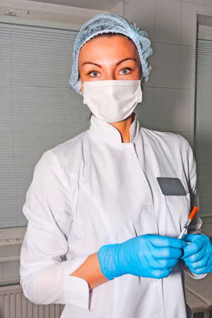 Dermatologist cosmetologist waits her patient with surgical mask, surgical cap and surgical gloves