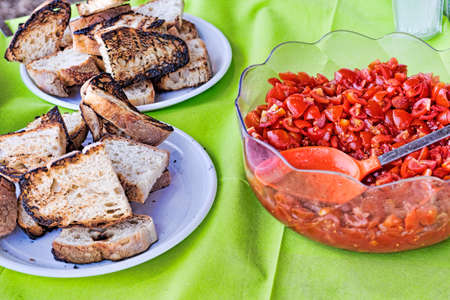 Table set to preparation of the typical Italian bruschetta with toasted bread, garlic and extra-virgin olive oil and diced tomatoes