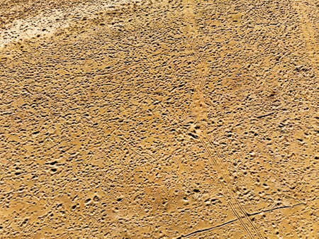 Aerial view of desert pink sand studded with footprints and tire tracks Imagens